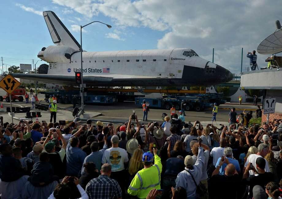 Spectators take pictures of the Space Shuttle Endeavour as it slowly moves along city streets in Los Angeles. Photo: Mark J. Terrill / Associated Press