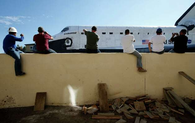 Construction workers watch as the Space Shuttle Endeavour moves along the street on a 160-wheeled carrier in Los Angeles. Photo: Jae C. Hong / Associated Press