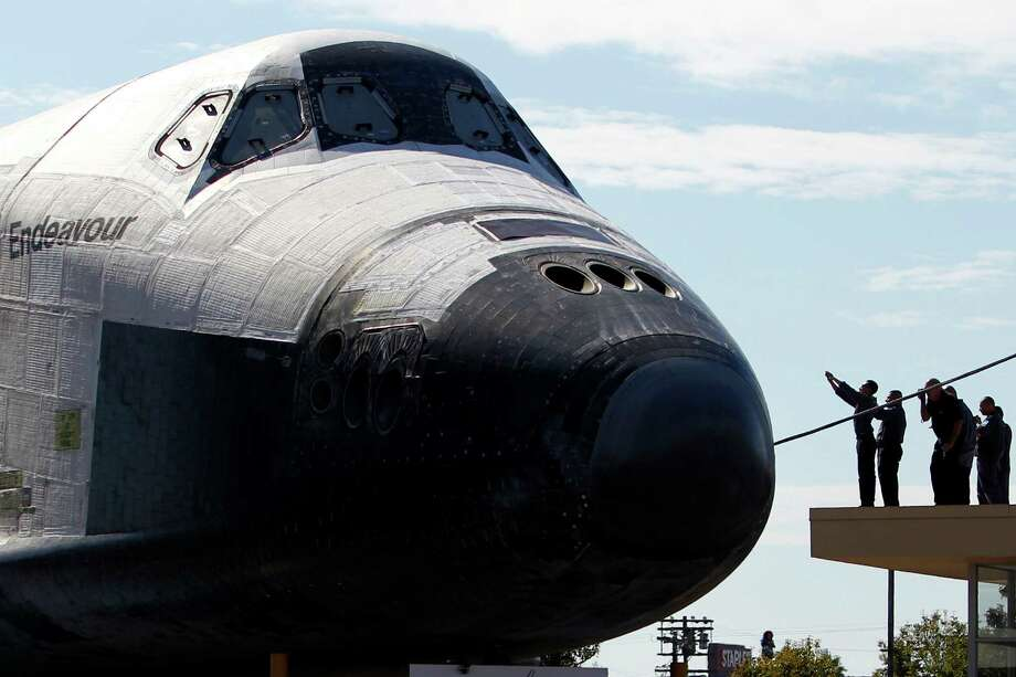 Spectators gather as the space shuttle Endeavour slowly moves along city streets. Photo: Patrick T. Fallon / Associated Press