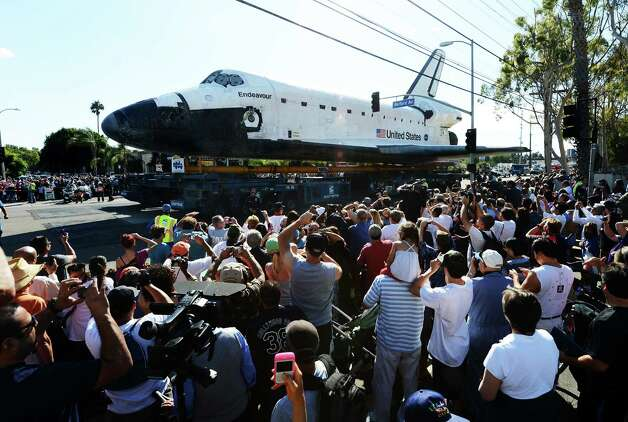 Crowds of people watch as watch as the Space Shuttle Endeavour is transported through the streets of Los Angeles. Photo: Robyn Beck / AFP/Getty Images