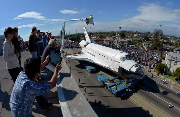 A crowd watches the Space Shuttle Endeavour as it is slowly moved along a city street. Photo: Mark J. Terrill / Associated Press