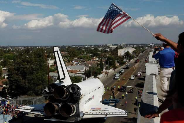 Jose Salazar waves an American flag as he and other spectators gathered on a roof watch the space shuttle Endeavour slowly move along city streets. Photo: Patrick T. Fallon / Associated Press