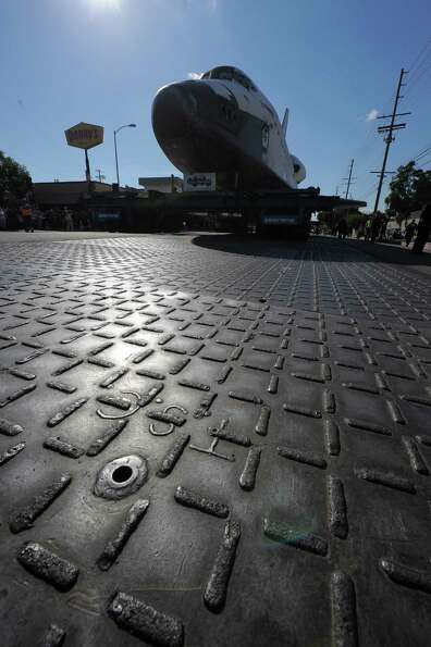 Space Shuttle Endeavour rolls over steel plates put down to protect the streets.