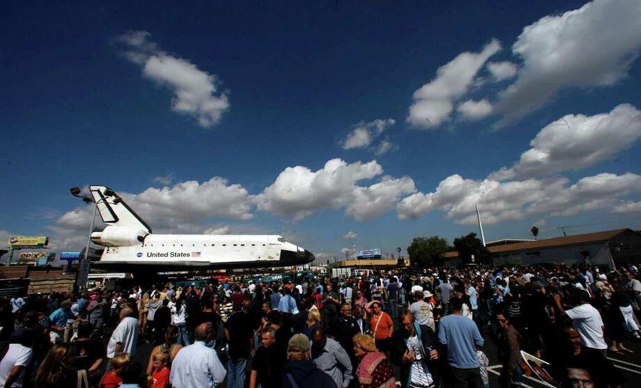 Crowds gather to get a view of the parked space shuttle Endeavour in a parking lot. Photo: Genaro Molina / Los Angeles Times/via Associated Press