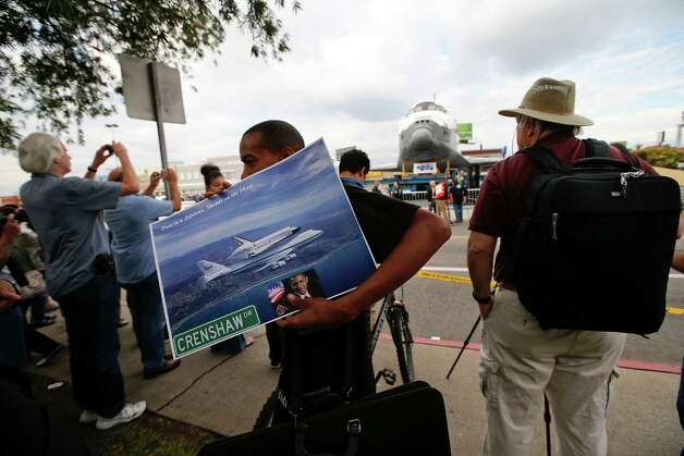 Vendor Mitch Warner sells the space shuttle Endeavour posters as spectators gather. Photo: Jae C. Hong / Associated Press