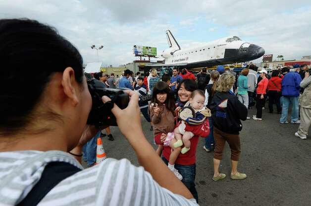 Mifumi Nakajima (L) takes a picture of her husband Nozomo Nakajima holding their children Leigha Nakajima, 3, and Eli Nakajima, 6 months, in front of the space shuttle Endeavour parked in a mall parking lot. Photo: Kevork Djansezian / Getty Images