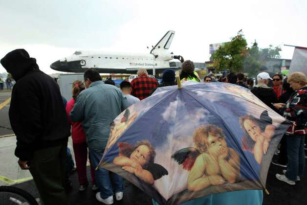 People get a close view of the space shuttle Endeavour in a misty rain during a break in its movement as it is transported from Los Angeles International Airport (LAX) to the California Science Center in Exposition Park. Photo: David McNew / Getty Images