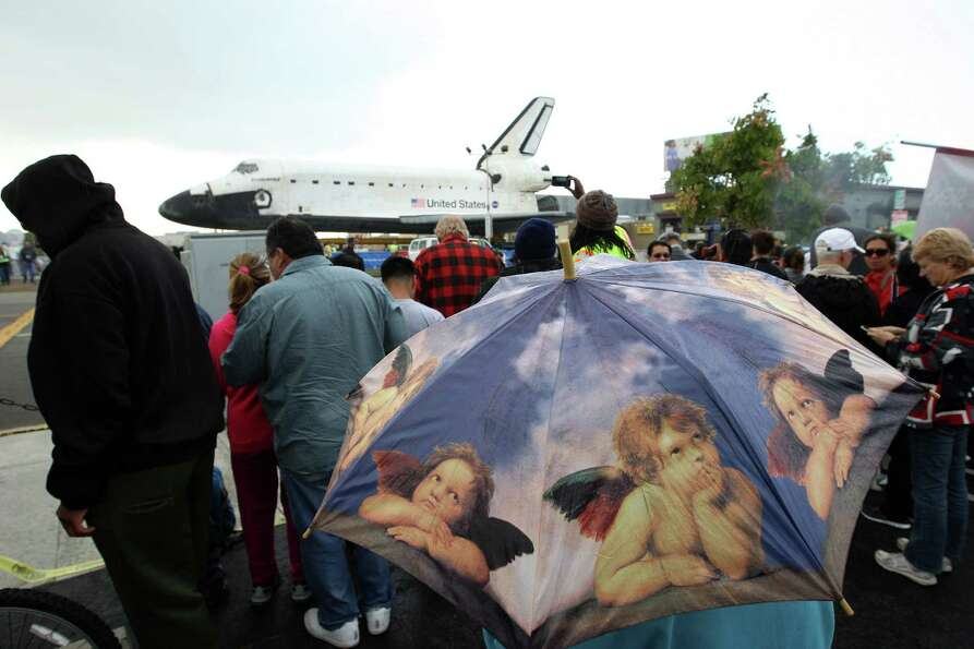 People get a close view of the space shuttle Endeavour in a misty rain during a break in its movemen