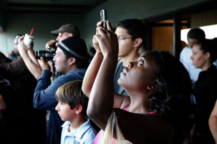 Members of the public photograph the space shuttle Endeavour.
