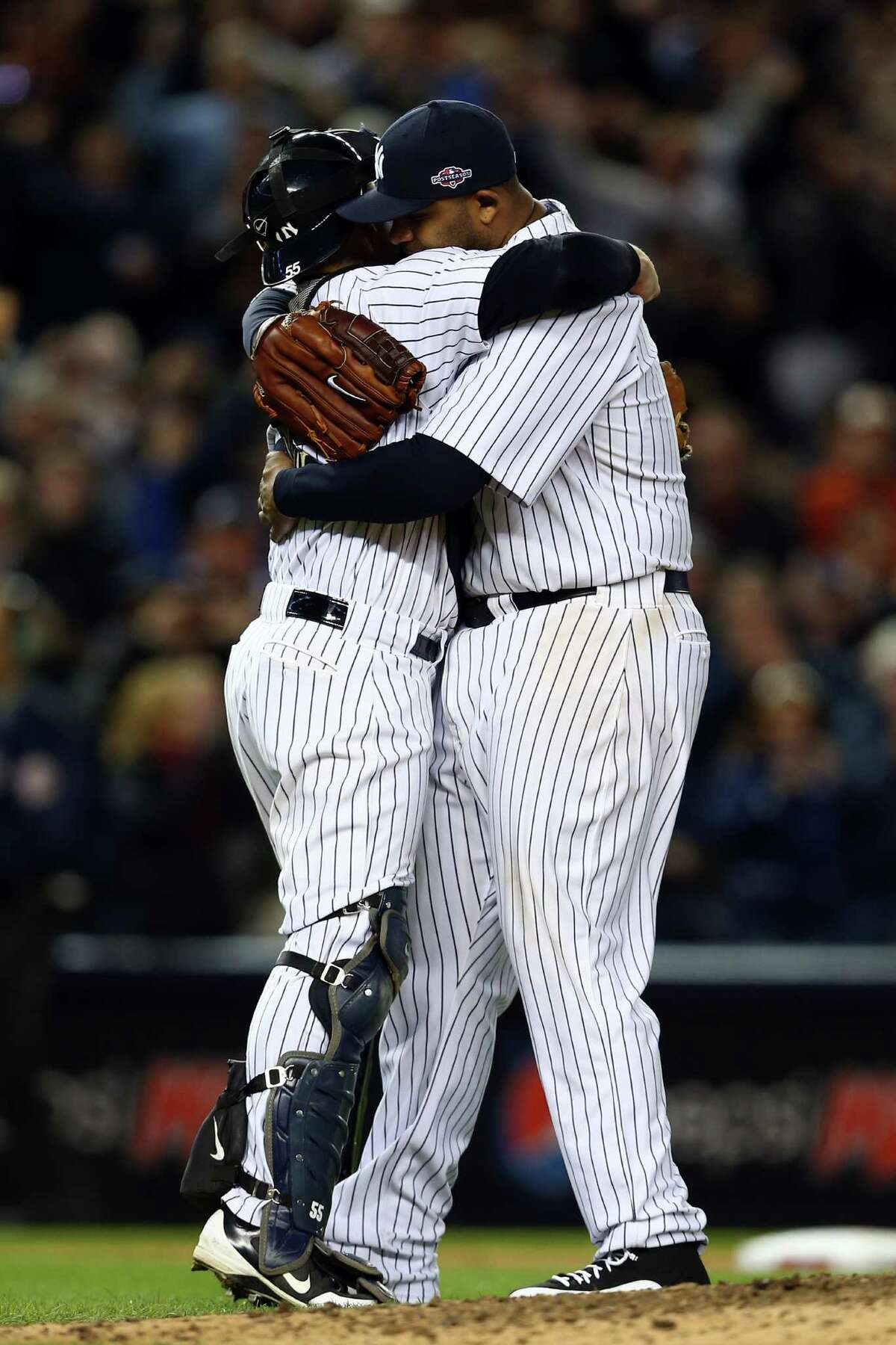 NEW YORK, NY - OCTOBER 12: CC Sabathia #52 and Russell Martin #55 of the New York Yankees celebrate after defeating the Baltimore Orioles by a score of 3-1 to win Game Five of the American League Division Series at Yankee Stadium on October 12, 2012 in New York, New York.