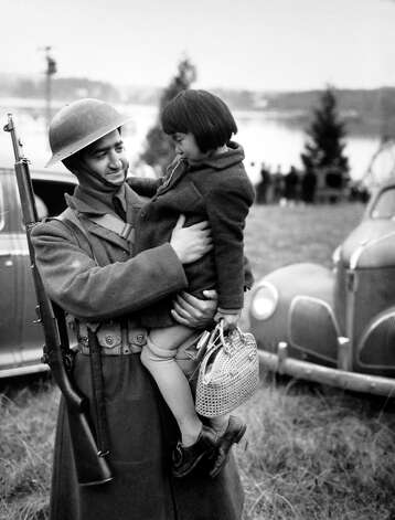 A soldier holds a Japanese American girl on Bainbridge Island on March 30, 1942, during the internment of Japanese Americans from Bainbridge Island. They were the first group incarcerated in the country under Executive Order 9066. Photo: MOHAI/seattlepi.com File,  -