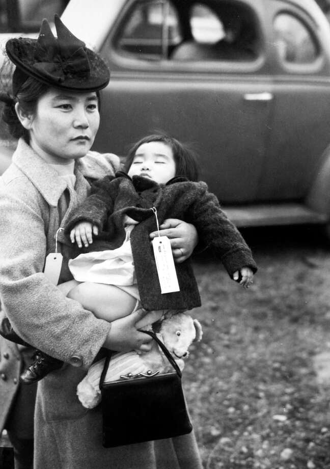 With her daughter asleep in her arms, Fumiko Hayashida waits to board a ferry from Bainbridge Island on March 30, 1942. The pair were being deported to an internment camp for Japanese-Americans in Manzanar, Calif. This image, taken by a P-I photographer, has been published around the world and since 1976 the negative has been preserved at the Museum of History and Industry. Years ago, staff there helped identify Hayashida by enlarging the photo and reading the tags she and her daughter wore. Photo: Seattlepi.com File/MOHAI, -