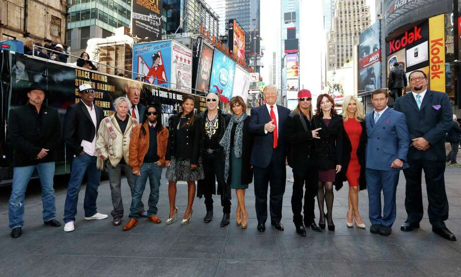 "This image released by NBC shows the new cast of ""All-Star Celebrity Apprentice,"" from left, Trace Adkins, Dennis Rodman, Gary Busey, Lil Jon, Claudia Jordan, Dee Snider, Lisa Rinna, show creator Donald Trump, Bret Michaels, Marilu Henner, Brande Roderick, Stephen Baldwin and Penn Jillette, posing in New York's Times Square, Friday, Oct. 12, 2012. The cast, all contestants on previous  seasons of ""Celebrity Apprentice"", will begin taping on Monday, Oct. 15, for the new season airing in March.  (AP Photo/NBC, Heidi Gutman) Photo: Heidi Gutman"