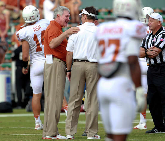 Mack Brown chats with Oklahoma head coach Bob Stoops at Longhorn quarterback David Ash warms up pregame as UT Oklahoma in the Red River Rivalry at the Cotton Bowl on October 13, 2012. Photo: Tom Reel, Express-News / ©2012 San Antono Express-News