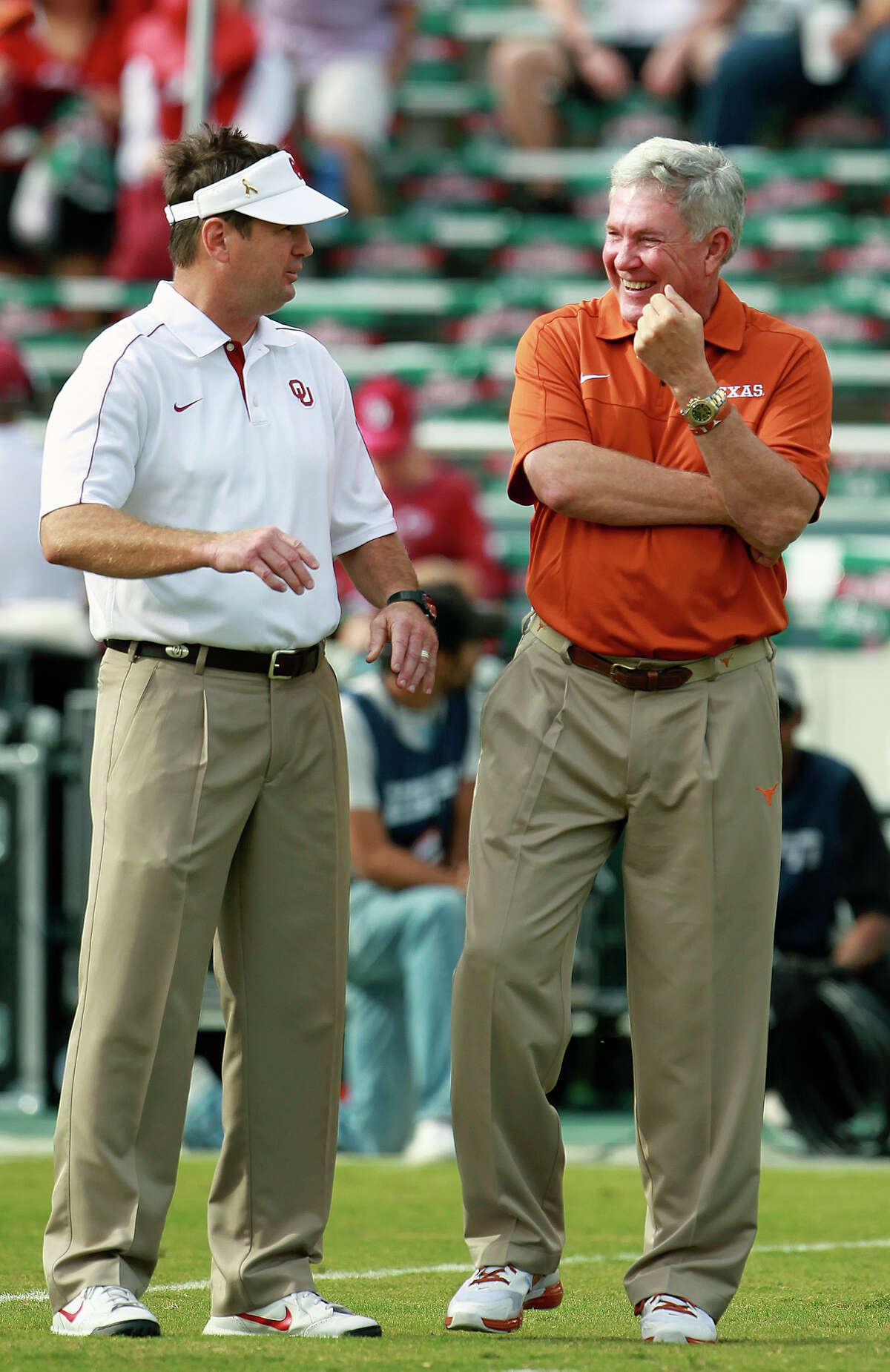 Bob Stoops and Mack Brown enjoy a pregame chat as UT Oklahoma in the Red River Rivalry at the Cotton Bowl on October 13, 2012.