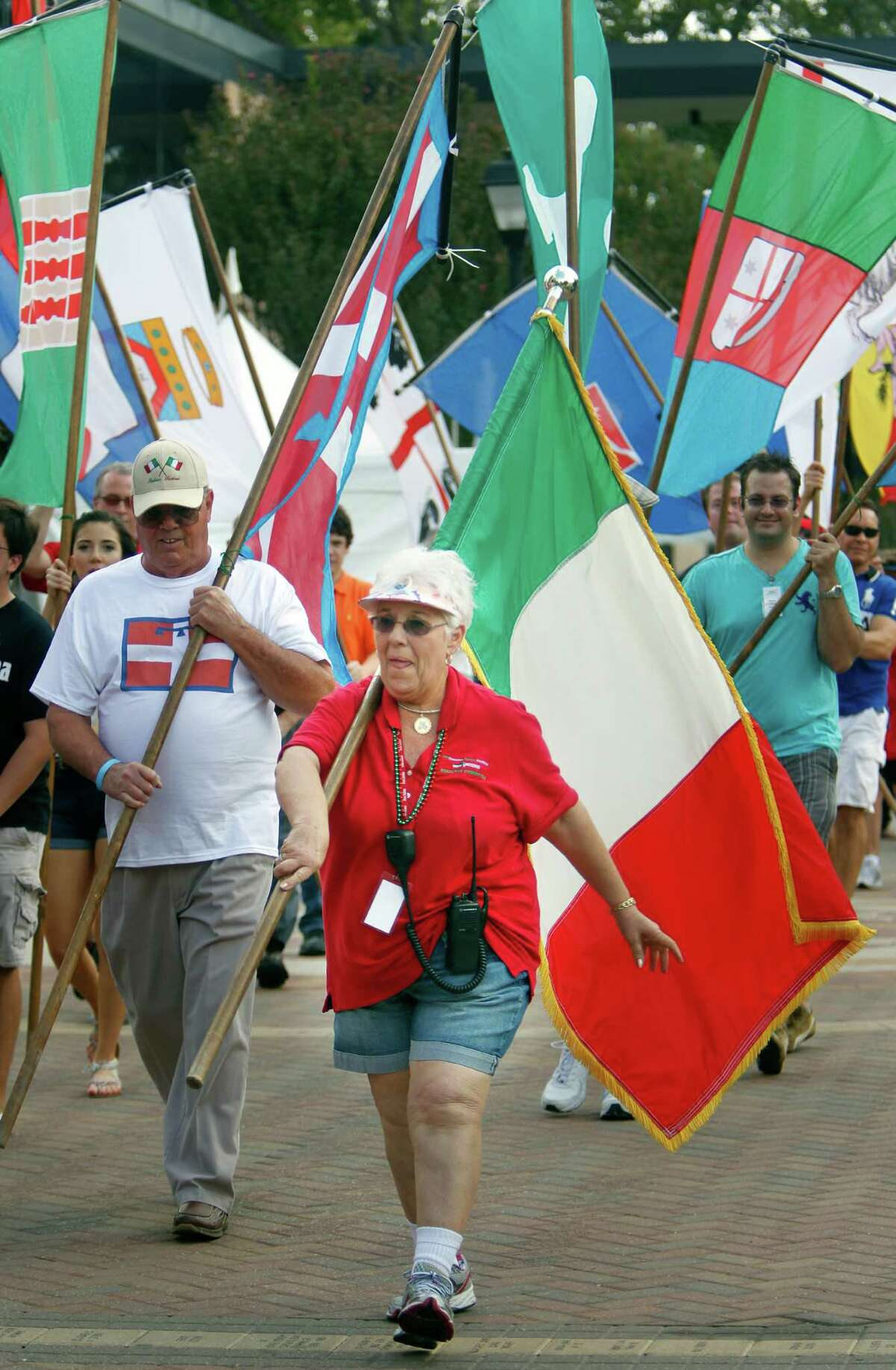 Margie Dipuma, center, awarded ICCC's Christopher Columbus Award, carries the Italian Flag during the Flag Ceremony & Awards to start the 34th Houston Italian Festival at the University of St. Thomas on Saturday.
