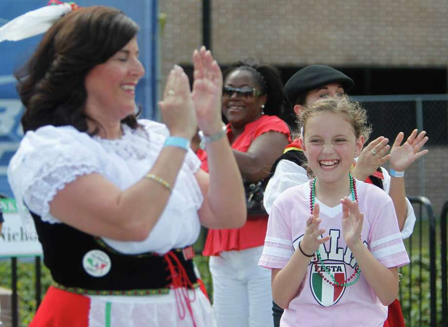 Gracie Shear, 11, joins the fun in the audience participation portion with the Italian Tarantellas, Italian Folk Dancing, during the 34th Houston Italian Festival at University of St. Thomas on Saturday, Oct. 13, 2012, in Houston. The Italian Tarantellas, Italian Folk Dancing, will perform Sunday 12:30 p.m. Festival sponsored by the Italian Cultural & Community Center (ICCC), and it runs until Sunday. Photo: Mayra Beltran, Houston Chronicle / © 2012 Houston Chronicle