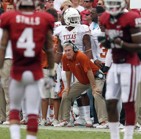 Texas Longhorns head coach Mac Brown (center) is seen between two Oklahoma players in the first half at the Red River Rivalry at the Cotton Bowl in Dallas on Saturday, Oct. 13, 2012. Photo: Kin Man Hui, Express-News / © 2012 San Antonio Express-News