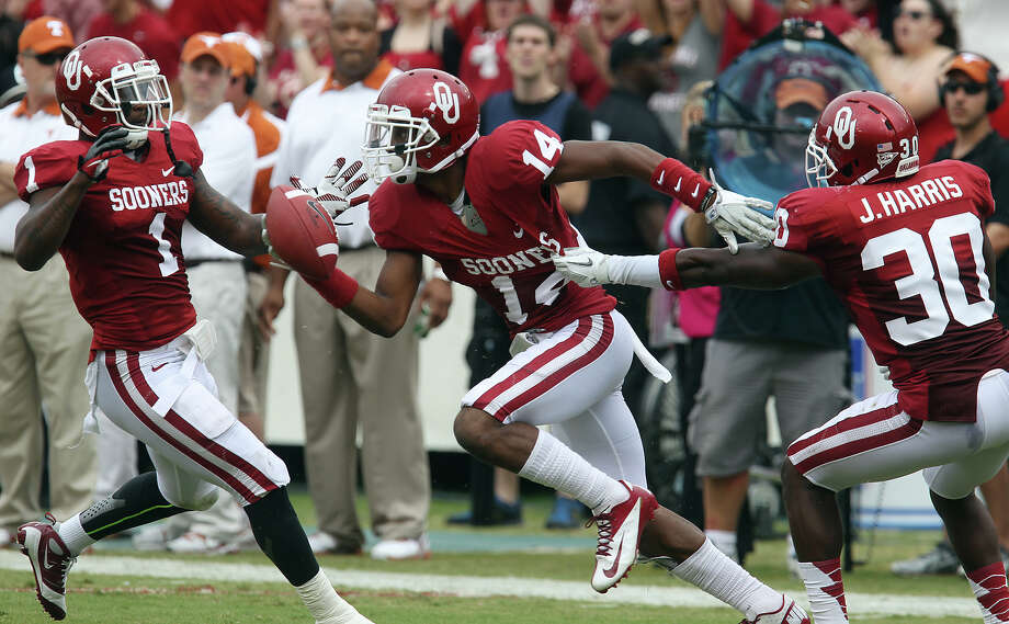 Oklahoma Sooners' Aaron Colvin (14) reacts after he intercepts a pass with teammates Tony Jefferson (01) and Javon Harris (30) against theTexas Longhorns in the first half at the Red River Rivalry at the Cotton Bowl in Dallas on Saturday, Oct. 13, 2012. Photo: Kin Man Hui, Express-News / © 2012 San Antonio Express-News
