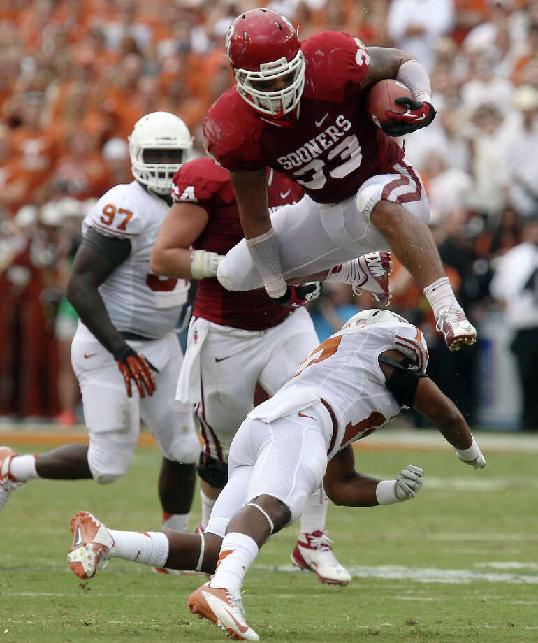 Oklahoma Sooners' Trey Millard (33) leaps over Texas Longhorns' Adrian Phillips (17) in the first half at the Red River Rivalry at the Cotton Bowl in Dallas on Saturday, Oct. 13, 2012. Photo: Kin Man Hui, Express-News / © 2012 San Antonio Express-News