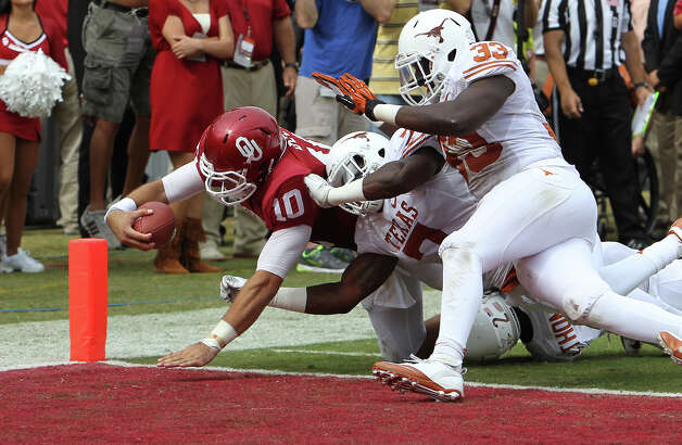Oklahoma Sooners quarterback Blake Bell (10) dives for the Sooners first score against Demarco Cobbs (07), Mykkele Thompson (02) and Steve Edmond (33) in the first half at the Red River Rivalry at the Cotton Bowl in Dallas on Saturday, Oct. 13, 2012. Photo: Kin Man Hui, Express-News / © 2012 San Antonio Express-News
