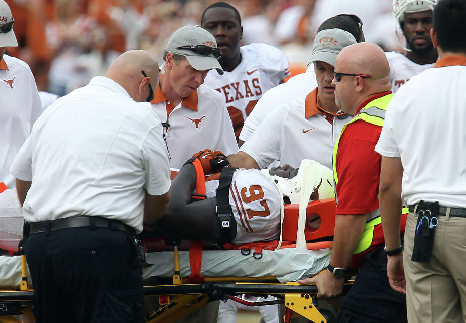 Texas Longhorns' Brandon Moore (97) receives medical help after an on-field injury in the game against the Oklahoma Sooners in the second half at the Red River Rivalry at the Cotton Bowl in Dallas on Saturday, Oct. 13, 2012. The Sooners defeated the Longhorns 63-21. Photo: Kin Man Hui, Express-News / © 2012 San Antonio Express-News