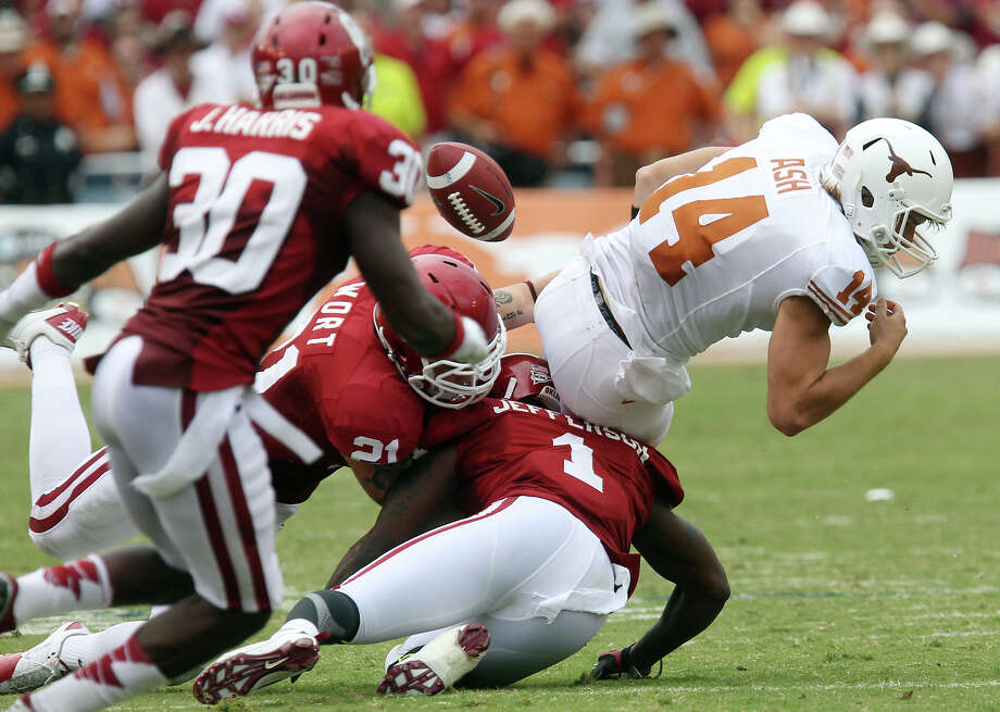 Texas Longhorns quarterback David Ash (14) fumbles the ball while tackled by Oklahoma Sooners' Tom Wort (21) and Tony Jefferson (01) in the second half at the Red River Rivalry at the Cotton Bowl in Dallas on Saturday, Oct. 13, 2012. The Sooners defeated the Longhorns 63-21. Photo: Kin Man Hui, Express-News / © 2012 San Antonio Express-News