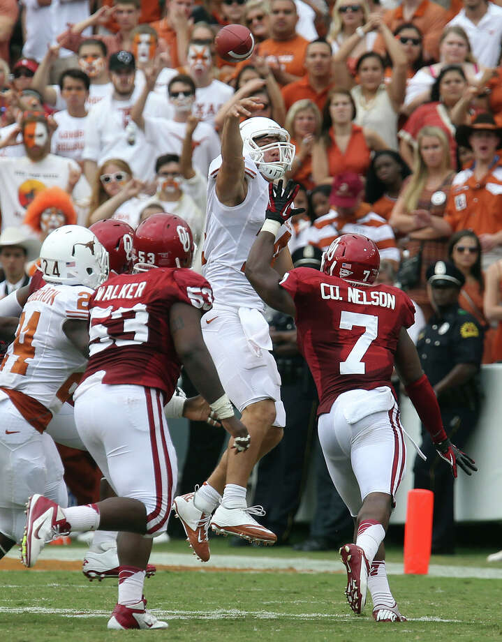 Texas Longhorns' quarterback David Ash (center) attempts a throw over Oklahoma Sooners' Casey Walker (53) and Corey Nelson (07) in the second half at the Red River Rivalry at the Cotton Bowl in Dallas on Saturday, Oct. 13, 2012. The Sooners defeated the Longhorns 63-21. Photo: Kin Man Hui, Express-News / © 2012 San Antonio Express-News