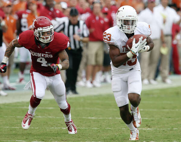 Texas Longhorns' Carrington Byndom (23) intercepts a pass against Oklahoma Sooners' Kenny Stills (04) and returns it for a touchdown in the second half at the Red River Rivalry at the Cotton Bowl in Dallas on Saturday, Oct. 13, 2012. The Sooners defeated the Longhorns 63-21. Photo: Kin Man Hui, Express-News / © 2012 San Antonio Express-News