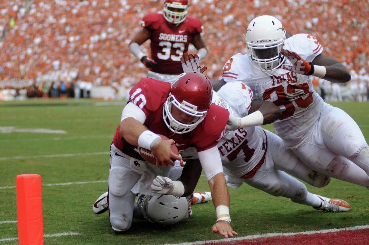 Oklahoma quarterback Blake Bell (10) stretches for the gaol line scoring a touchdown against Texas linebacker Steve Edmond (33), defensive back Mykkele Thompson (2) and linebacker Demarco Cobbs (7) during the first half of an NCAA college football game at the Cotton Bowl Saturday, Oct. 13, 2012, in Dallas. (AP Photo/The Daily Texan, Lawrence Peart)