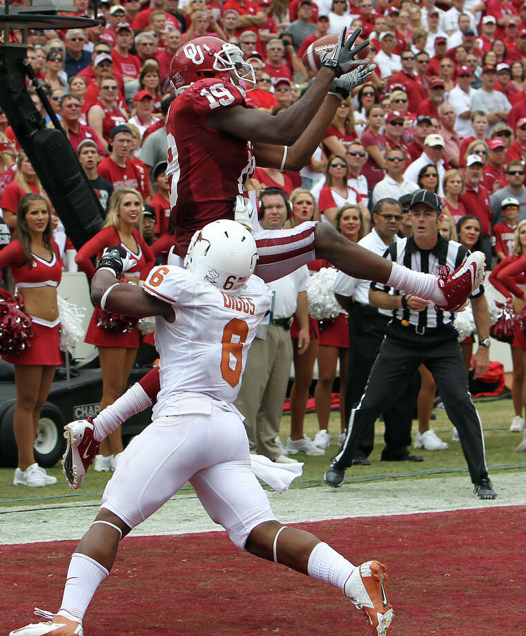 Oklahoma Sooners' Justin Brown (19) makes a catch in the end zone for a touchdown against Texas Longhorns' Quandre Diggs (06) in the second half at the Red River Rivalry at the Cotton Bowl in Dallas on Saturday, Oct. 13, 2012. The Sooners defeated the Longhorns 63-21. Photo: Kin Man Hui, Express-News / © 2012 San Antonio Express-News