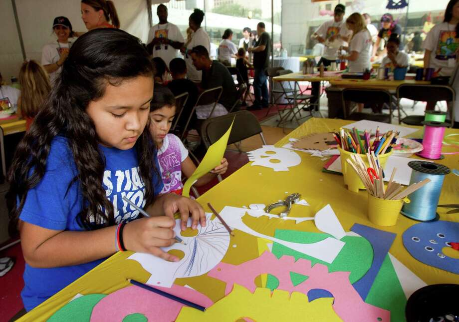 Adela Acosta, 12, and Alyssa Trejo make masks out of construction paper in the Creative Zone during the Bayou City Art Festival Saturday, Oct. 13, 2012, in Houston. Photo: Brett Coomer, Houston Chronicle / © 2012 Houston Chronicle