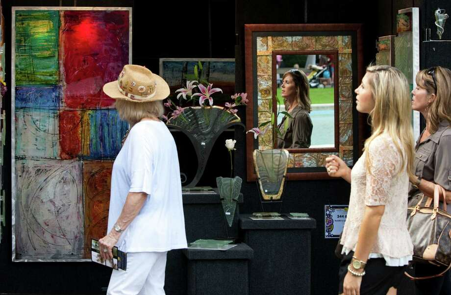 Patrons of the Bayou City Art Festival walk past Lyn & Randy Sedlak-Ford's booth Saturday, Oct. 13, 2012, in Houston. Photo: Brett Coomer, Houston Chronicle / © 2012 Houston Chronicle
