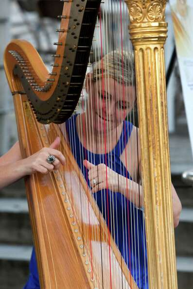 Merry Miller plays the harp during the Bayou City Art Festival Saturday, Oct. 13, 2012, in Houston.