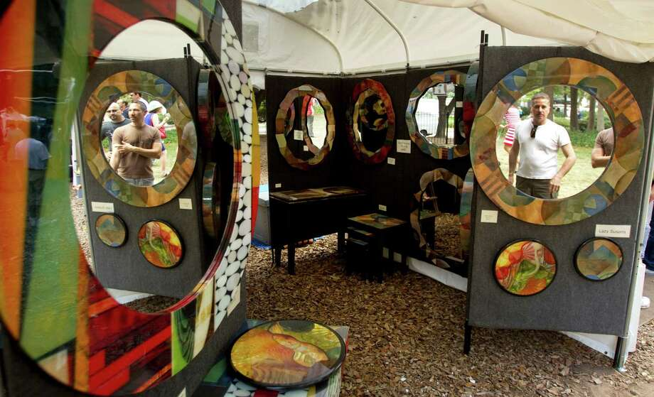 Visitors to Robert Cornell's booth are reflected on its mirrors during the Bayou City Art Festival Saturday, Oct. 13, 2012, in Houston. Photo: Brett Coomer, Houston Chronicle / © 2012 Houston Chronicle