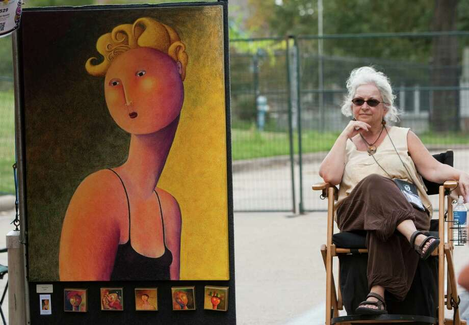 Carol Ferony, of DeFuniak Springs, Fla., sits next to one of her works of art during the Bayou City Art Festival Saturday, Oct. 13, 2012, in Houston. Photo: Brett Coomer, Houston Chronicle / © 2012 Houston Chronicle