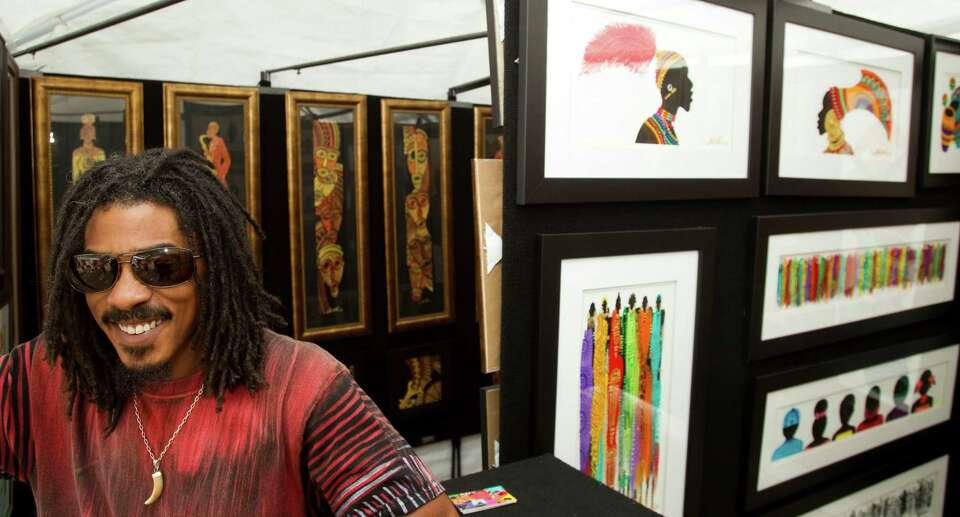 Kwesi Nabate, of Atlanta, sits in the Stuart McClean Gallery booth during the Bayou City Art Festiva