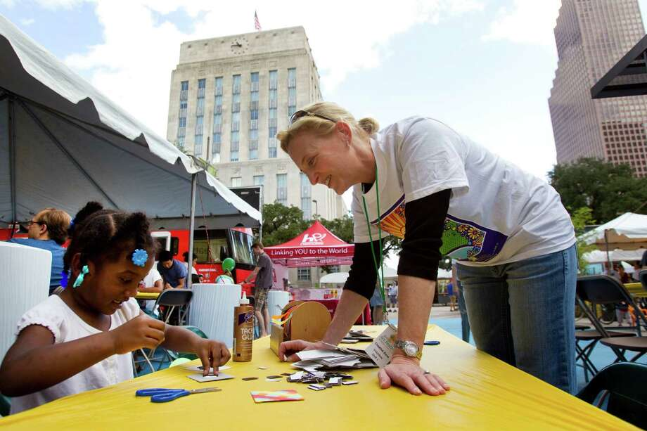 Keijah Lewis, 3, left, is helped with an art project by volunteer Kilby Hoskins in the Creative Zone at the Bayou City Art Festival Saturday, Oct. 13, 2012, in Houston. Photo: Brett Coomer, Houston Chronicle / © 2012 Houston Chronicle