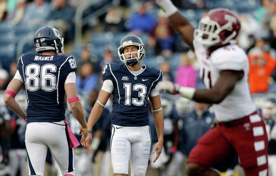 Temple defensive end Marcus Green, right, runs up the field as Connecticut kicker Chad Christen (13) reacts with teammate Cole Wagner (86) after Christen missed a field goal in overtime during an NCAA football game in East Hartford, Conn., Saturday, Oct. 13, 2012. Temple won 17-14. (AP Photo/Michael Dwyer) Photo: Michael Dwyer, Associated Press / AP