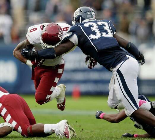 Connecticut linebacker Yawin Smallwood (33) tackles Temple running back Montel Harris (8) in overtime during an NCAA college football game in East Hartford, Conn., Saturday, Oct. 13, 2012. Temple won 17-14. (AP Photo/Michael Dwyer) Photo: Michael Dwyer, Associated Press / AP