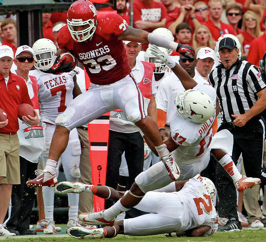 Trey Millard pops up in the air past two Longhorn tacklers in the first half and gets a long gain as UT plays Oklahoma in the Red River Rivalry at the Cotton Bowl on October 13, 2012. Photo: Tom Reel, Express-News / ©2012 San Antono Express-News