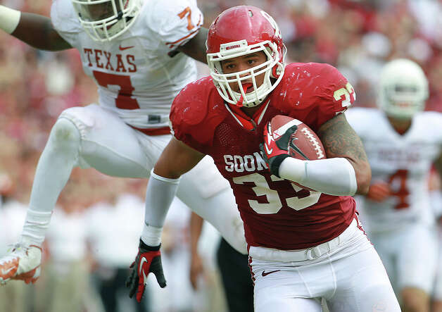 Sooner running back Trey Millard leaves Demarco Cobbs in the air as he darts in for a score in the second half as UT plays Oklahoma in the Red River Rivalry at the Cotton Bowl on October 13, 2012. Photo: Tom Reel, Express-News / ©2012 San Antono Express-News