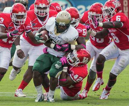 UAB running back Darrin Reaves (5) is brought down by Houston linebacker Phillip Steward (42) and a host of other Houston defenders during the first half of a college football game at Robertson Stadium, Saturday, Oct. 13, 2012, in Houston. Photo: Smiley N. Pool, Houston Chronicle / © 2012  Houston Chronicle