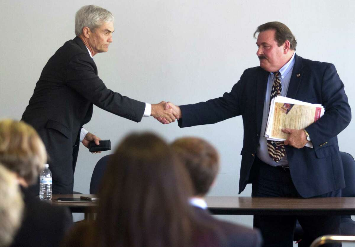 Harris County District Attorney candidates Mike Anderson, left and Lloyd Oliver shake hands after speaking with the Harris County Domestic Violence Coordinating Council on Thursday.