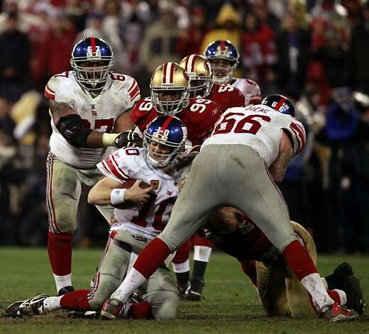 Aldon Smith and Justin Smith (partly hidden) take down Eli Manning in January's NFC title game. Photo: Lance Iversen, The Chronicle