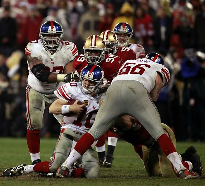 Aldon Smith and Justin Smith (partly hidden) take down Eli Manning in January's NFC title game.