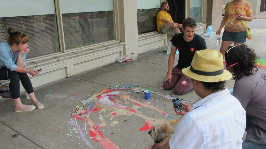 Aldon Mines discusses his piece with people attending Chalk It Up on Saturday.. Photo: Benjamin Olivo/mySA.com