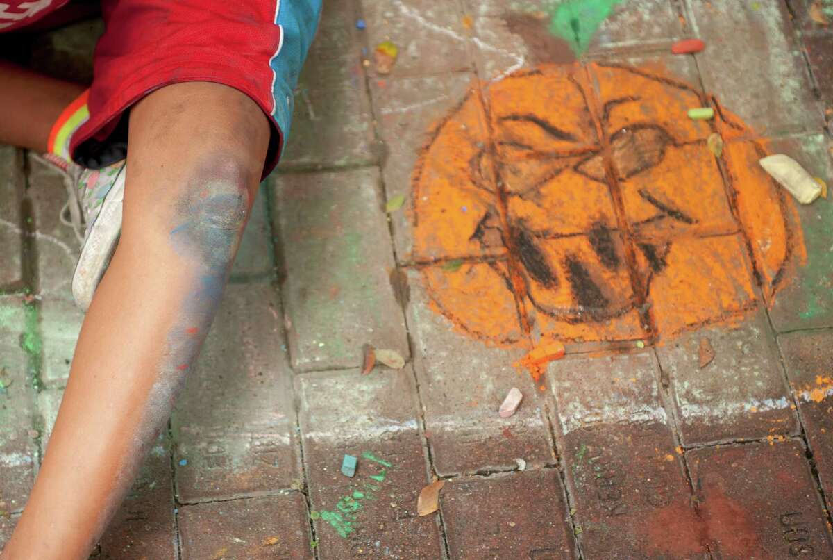The legs of a Harlandale Middle School student are covered in chalk as she works on a mural during Artpace's Chalk It Up, Saturday, Oct. 13, 2012, in Downtown San Antonio.
