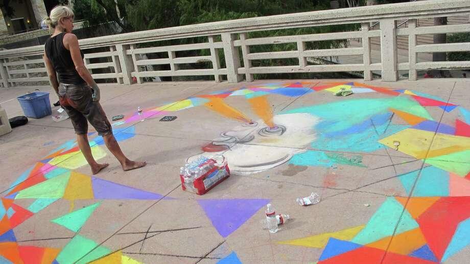 Katie Pell observes her piece at Chalk It Up on Saturday. Photo: Benjamin Olivo/mySA.com