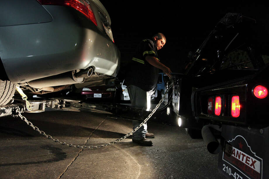 Johnny Martinez unhooks a car that he'd towed from the Oakhampton Place Apartments in his company's lot. Martinez works for Atlas Towing & Storage, one of San Antonio's many private towing companies. Photo: Edward A. Ornelas, San Antonio Express-News / © 2012 San Antonio Express-News